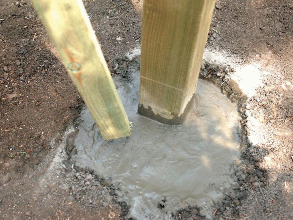 Зафиксируйте столбики в нужном положении и залейте ямы цементным раствором.